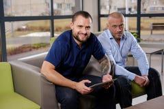 Сотрудники дела сидя на кресле в офисе и смотря камеру стоковая фотография rf