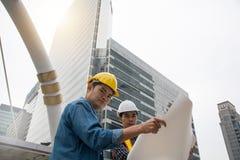 Сотрудники инженера обсуждая двигать вперед план стоковая фотография