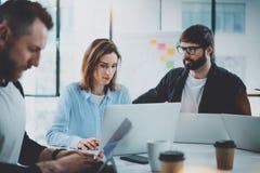 Сотрудники объединяются в команду работа с мобильным компьютером на современном офисе горизонтально стоковое фото