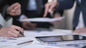 Сотрудники подготавливая бизнес-план для роста компании, профессиональной сыгранности акции видеоматериалы