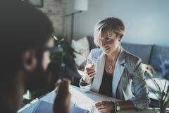 Сотрудники работая процесс дома Молодая белокурая женщина работая вместе с бородатым человеком коллеги на современном домашнем оф Стоковые Изображения