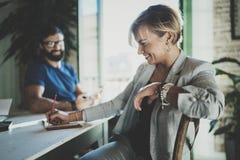 Сотрудники работая процесс дома Молодая белокурая женщина работая вместе с бородатым человеком коллеги на современном домашнем оф Стоковые Изображения RF