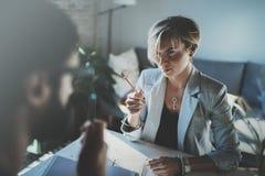 Сотрудники работая процесс дома Молодая белокурая женщина работая вместе с бородатым человеком коллеги на современном домашнем оф Стоковые Фотографии RF