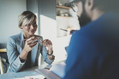 Сотрудники работая процесс дома Молодая белокурая женщина работая вместе с бородатым человеком коллеги на современном домашнем оф Стоковая Фотография RF