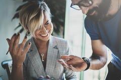 Сотрудники работая процесс дома Молодая белокурая женщина работая вместе с бородатым человеком коллеги на современном домашнем оф Стоковая Фотография