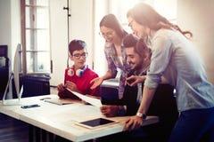 Сотрудники работая совместно в команде и обсуждая идеи Стоковое Фото