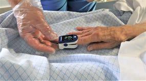 Сотрудник военно-медицинской службы и пациент используя оксиметр ИМПа ульс пальца стоковая фотография rf