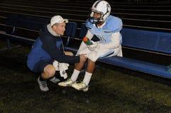 Сотрудник военно-медицинской службы команды проверяет футболиста средней школы стоковые изображения