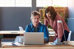 2 сотрудника говоря совместно над компьтер-книжкой в офисе Стоковые Фотографии RF