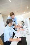 Сотрудники дела на офисе работая на таблетке и компьютере Стоковое Фото