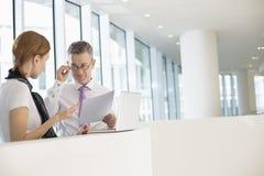 Сотрудники дела обсуждая работу в офисе Стоковые Изображения