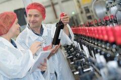 Сотрудник показывая заново произведенное вино бутылки на manufactory винодельни Стоковые Изображения RF
