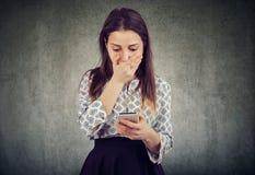 Сотрясенная девушка читая сообщение smartphone стоковое фото rf