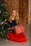 Сотрясенная девушка раскрывая подарок дома в живущей комнате Стоковое Изображение
