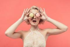 сотрясенная женщина в бюстгальтере шнурка держа 2 macarons перед глазами, стоковая фотография rf