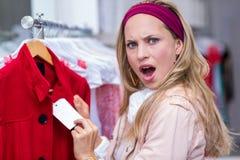 Сотрясенная женщина показывая ценник к камере Стоковое Изображение