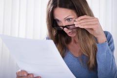 Сотрясенная женщина смотря документ в офисе стоковое изображение rf