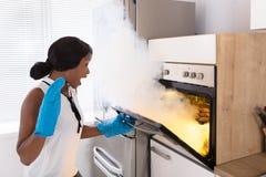 Сотрясенная женщина смотря, который сгорели печенья в печи стоковые фотографии rf