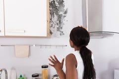 Сотрясенная женщина смотря прессформу на стене стоковая фотография