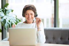 Сотрясенная зрелая женщина смотря компьютер стоковые фотографии rf