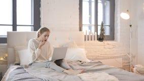 Сотрясенная маленькая девочка интересуя к результатам на ноутбуке в кровати сток-видео