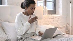 Сотрясенная молодая африканская женщина интересуя к результатам на ноутбуке в кровати сток-видео