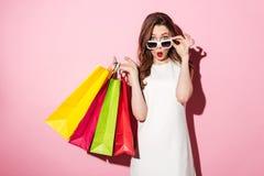 Сотрясенная молодая дама брюнет с хозяйственными сумками Стоковые Фотографии RF