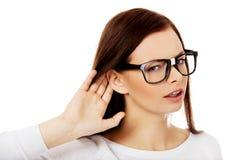 Сотрясенная молодая женщина подслушивая переговор стоковая фотография rf