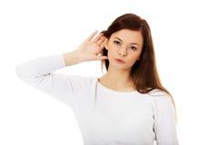 Сотрясенная молодая женщина подслушивая переговор стоковое изображение rf