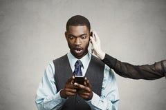 Сотрясенная плохая новость чтения бизнесмена на умном телефоне, пока havin стоковое изображение
