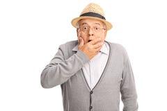 Сотрясенная старшая держа рука jhis на его рте стоковые изображения rf