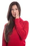 Сотрясенное красивое брюнет в длинном красном шлямбуре изолированном на белизне стоковое изображение rf