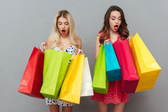 Сотрясенные детеныши 2 дамы с хозяйственными сумками Стоковые Фотографии RF