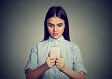 Сотрясенные новости женщины наблюдая на смартфоне стоковое изображение