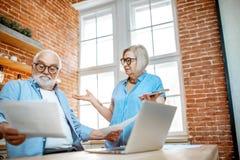Сотрясенные старшие пары со счетами дома стоковое фото