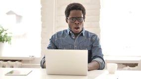 Сотрясенный африканский человек интересуя и работая на ноутбуке видеоматериал