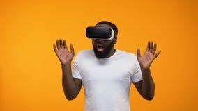 Сотрясенный Афро-американский человек изумленный симуляции виртуальной реальности, современное устройство сток-видео