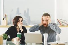 Сотрясенный бизнесмен и женщина работая на проекте Стоковое фото RF