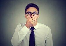 Сотрясенный молодой человек покрывая его рот с рукой стоковое изображение rf
