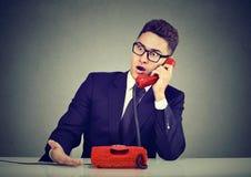Сотрясенный молодой человек получая плохую новость над телефоном стоковое фото rf