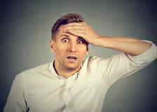 Сотрясенный молодой человек смотря камеру стоковое фото rf