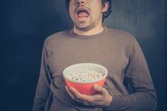 Сотрясенный молодой человек с попкорном стоковая фотография