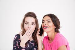 Сотрясенный переговор подслушивать женщины жизнерадостной женщины с мобильным телефоном Стоковое Изображение