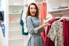 Сотрясенный покупатель молодой женщины в голубом платье в магазине Стоковая Фотография