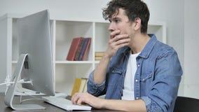 Сотрясенный творческий человек интересуя и работая на рабочем столе сток-видео