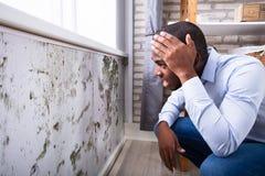 Сотрясенный человек смотря прессформу на стене стоковая фотография rf
