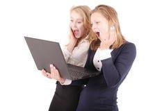 2 сотрясенных девушки используя компьтер-книжку Стоковое Изображение RF