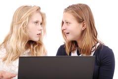 2 сотрясенных девушки используя компьтер-книжку Стоковая Фотография