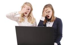 2 сотрясенных девушки используя компьтер-книжку Стоковые Изображения