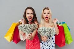 2 сотрясенных женщины держа хозяйственные сумки и показывая деньги Стоковая Фотография RF